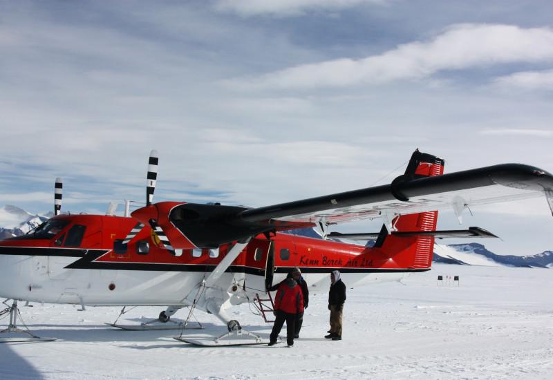 Eine rot-weiße Propellermaschine mit drei Kufen anstelle eines Fahrwerks mit Rädern steht auf einer weiten Schneefläche. Im Hintergrund sind Berge. Vor der Maschine stehen drei Personen.