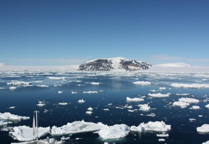 Die Aufnahme ist vom Bug eines Schiffes gemacht, so sind noch der vorderste Teil des Schiffes und dann das Südpolarmeer im Bild. Auf dem Wasser treiben Eisschollen und im Hintergrund ist antarktisches Festland.