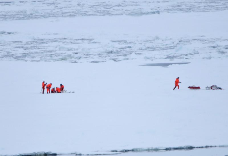 Auf einer weiten Eisebene steht eine Gruppe von Forschern und roten Kälteschutzanzügen. Sie entnehmen an einer Stelle eine Eisprobe. Weiter rechts läuft eine weitere Person zur Ausrüstung.