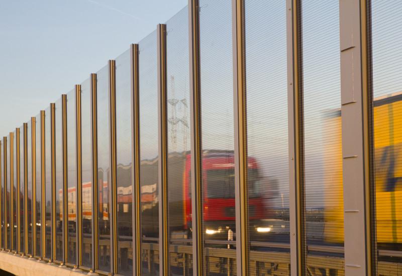 Lkws fahren auf der Autobahn hinter einer Lärmschutzwand.