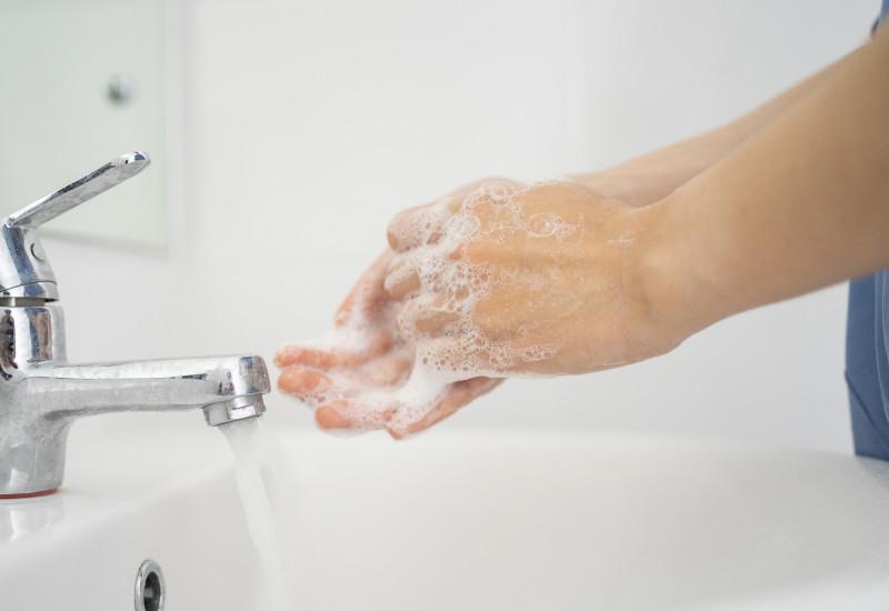 Eine Frau wäscht sich die Hände zur Händedesinfektion.
