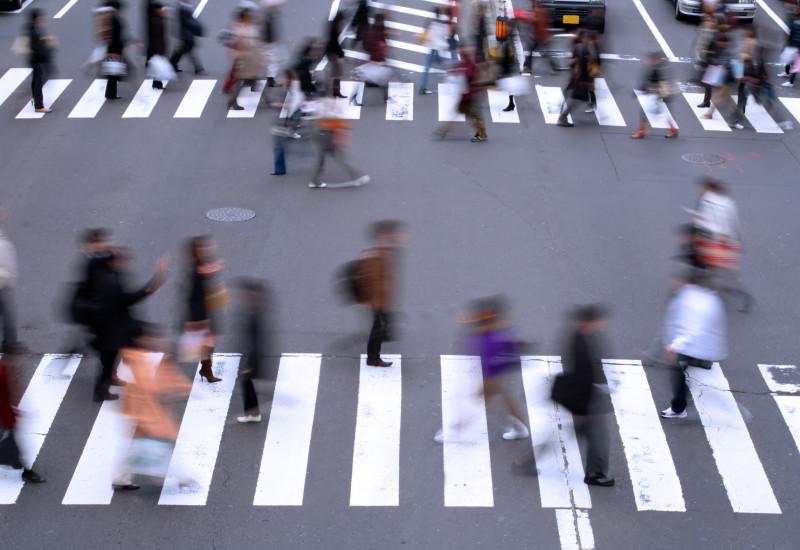 Fußgänger überqueren die Straße über einen Zebrastreifen.
