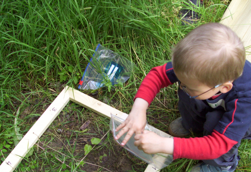 Ein Kind guckt sich den Boden innerhalb eines Holzrahmens ganz genau an und füllt eine Probe in eine Plastiktüte