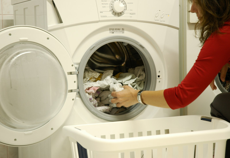Frau entnimmt Wäsche aus der Waschmaschine.