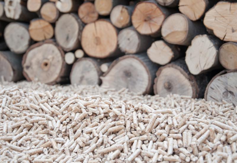 Holzpellets vor einem Holzstapel