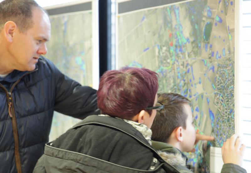 Familie schaut sich eine Landkarte an und der Vater zeigt seinem Sohn und seiner Ehefrau etwas auf der Karte, die aus der Luft fotografiert wurde und farbig markierte Bereiche hat