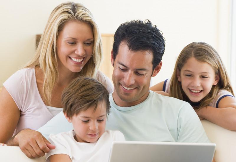 Familie sitzt auf dem Sofa und schaut zusammen auf den geöffneten Laptop