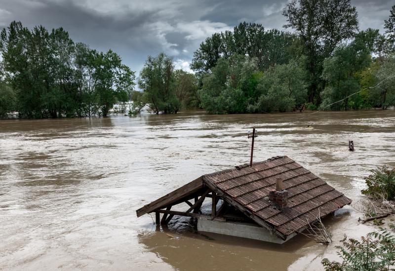 Bild zeigt eine überschwemmte Landfläche, auf welcher ein Schuppen stand; dieses ist jedoch überflutet