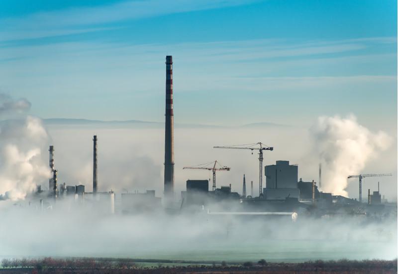 Industrieanlage mit mehreren Rauchtürmen und zwei Baukränen auf dem Gebiet; im Vordergrund steigt Nebel aus dem Kühlwasserflussauf