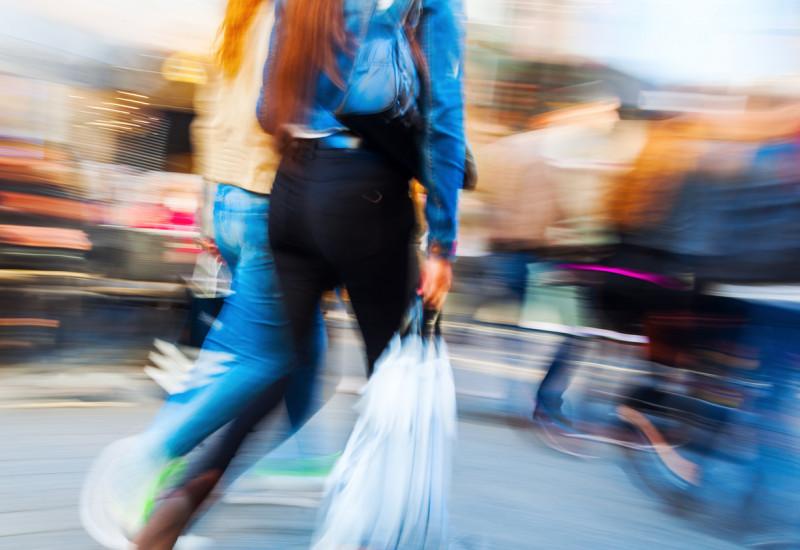 hektischer, verschwommener Hintergrund, der sich anscheinend dreht; im Mittelpunkt stehen zwei Frauen, die durch die Fußgängerzone schlendern und Einkaufstüten in ihren Händen tragen