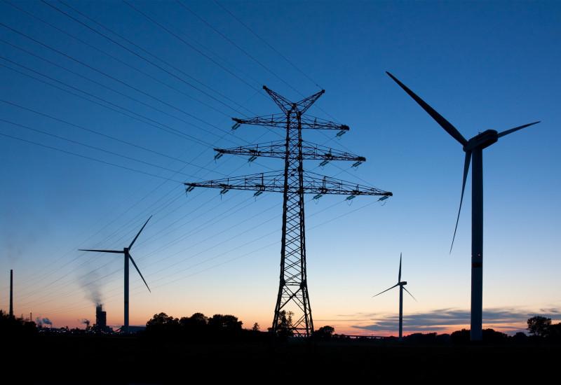 Stromstraße aus Windkraftanlagen in der Abenddämmerung