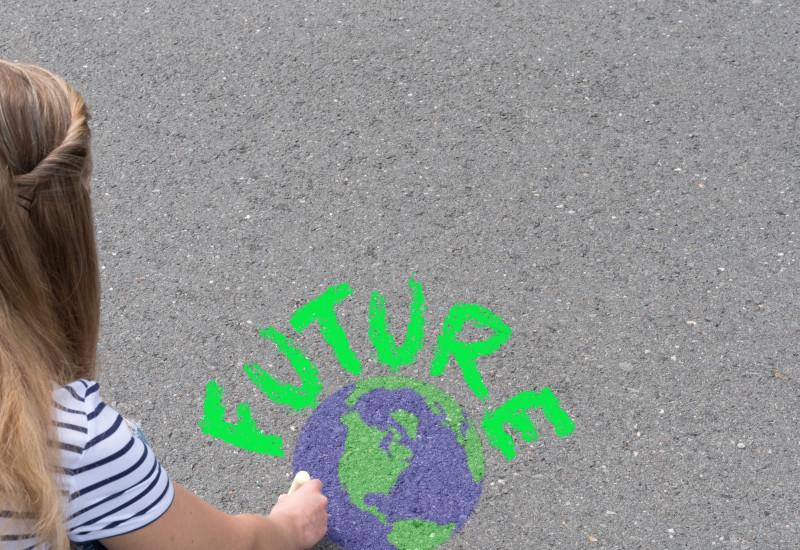 Symbolbild für den Klimaschutz. Weibliche Person malt mit Kreide die Erde und das Wort Future auf den Boden.
