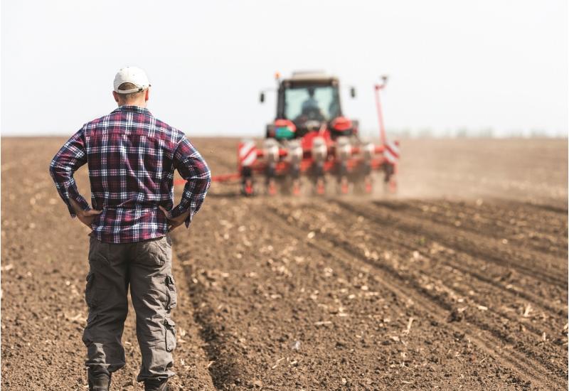 Das Bild zeigt einen Landwirt, der in einem Acker stehend einem Traktor bei der Einsaat hinterherblickt.