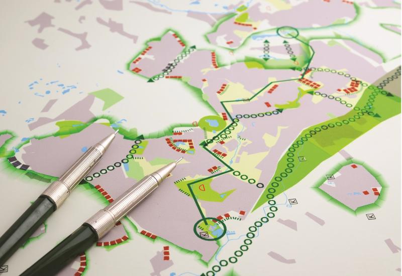 Das Bild zeigt einen Plan mit verschiedenen farbigen Plansymbolen und einen darauf liegenden Stift.
