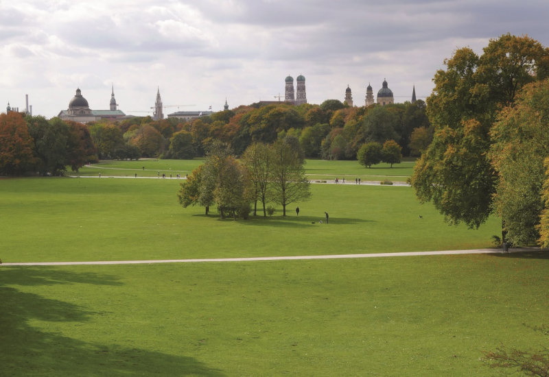 The picture shows a view of the English Garden in Munich. You can see large meadows criss-crossed by paths with individual groups of trees. In the background you can see the silhouette of Munich.