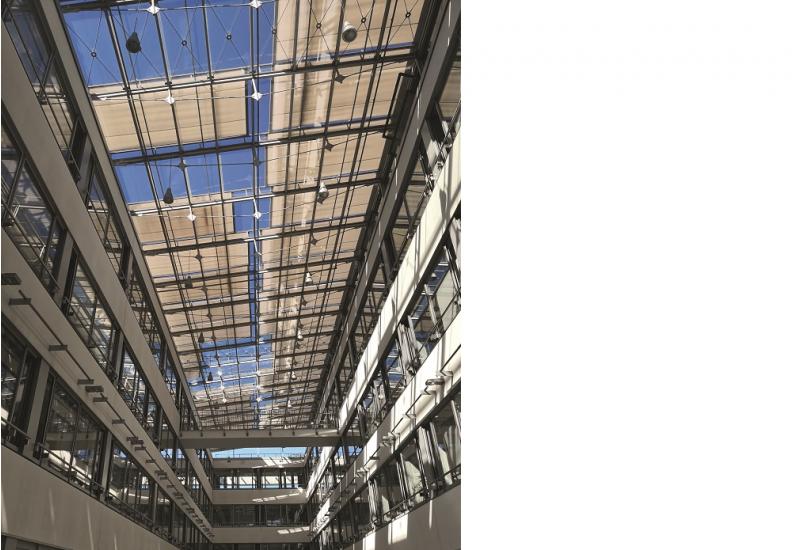 Das Bild zeigt den Blick zu gläsernen Dach eines Innenhofes eines modernen Gebäudes, das teilweise durch Textilbahnen verschattet wird.