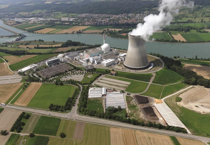 Das Bild zeigt das Luftbild eines Kernkraftwerks mit einem Wasserdampf absondernden Kühlturm am Rande eines Flusses.