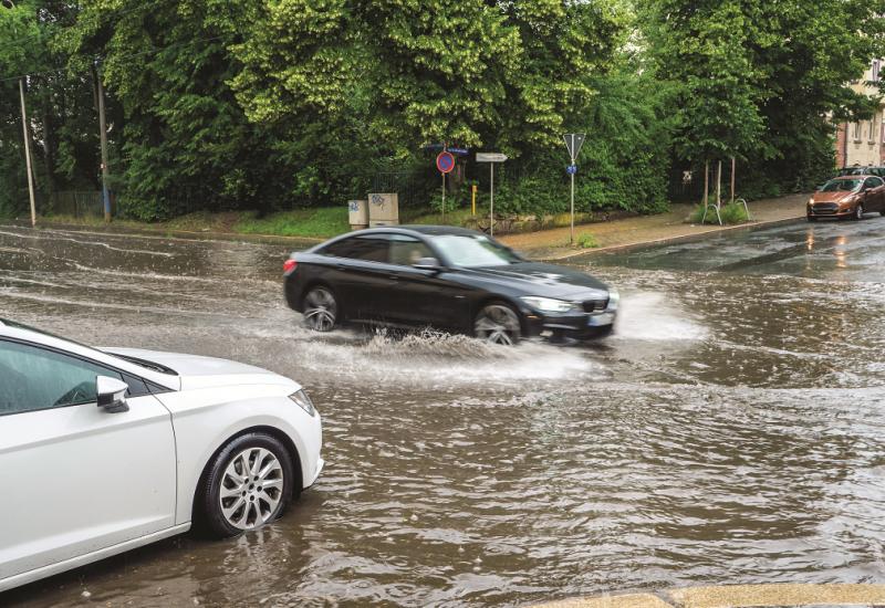 Das Bild zeigt eine völlig überflutete Straßenkreuzung in einer Stadt, in die gerade zwei Autos hineinfahren.