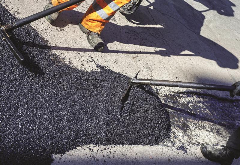 Das Bild zeigt die Beine eines Straßenbauarbeiters, der gerade eine Stück Straße mit frischem Asphalt ausbessert.
