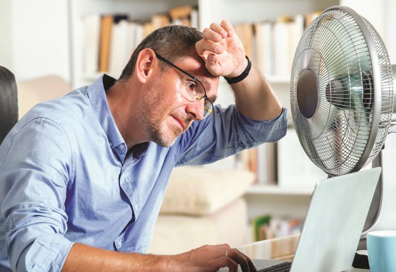 Das Bild zeigt einen Mann, der vor einem Ventilator in einem Büro sitzt und sich den Handrücken vor die Stirn hält.