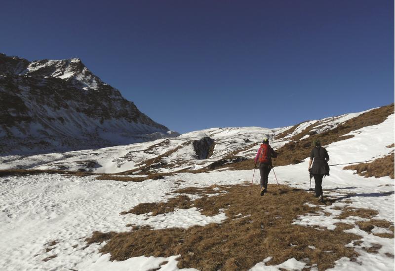 Das Bild zeigt zwei Bergsteigerinnen von hinten, die mit Stöcken über eine teilweise schneebedeckte Bergwiese wandern.