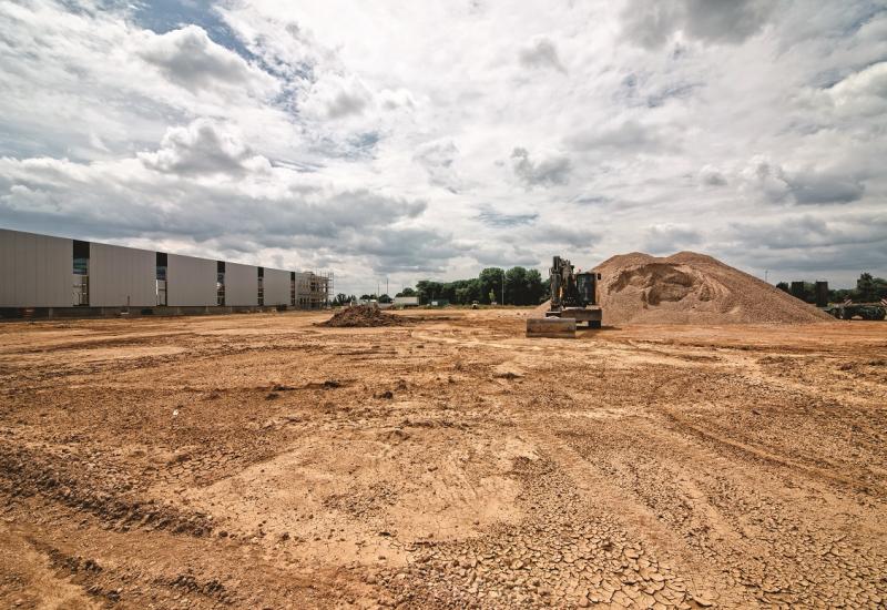 Das Bild zeigt eine große offene Bodenfläche auf einer Baustelle. Im Hintergrund steht rechts neben einem aufgeschütteten Erdhügel ein Bagger auf der Fläche, links sieht man Teile einer Industriehalle.