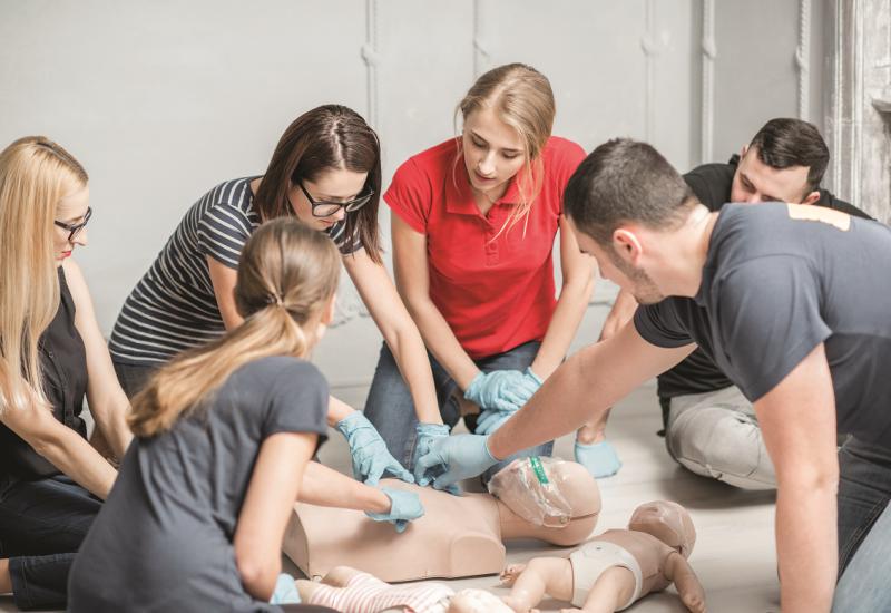 Das Bild zeigt eine Gruppe von drei Frauen und zwei Männern bei einer Erste-Hilfe-Übung.