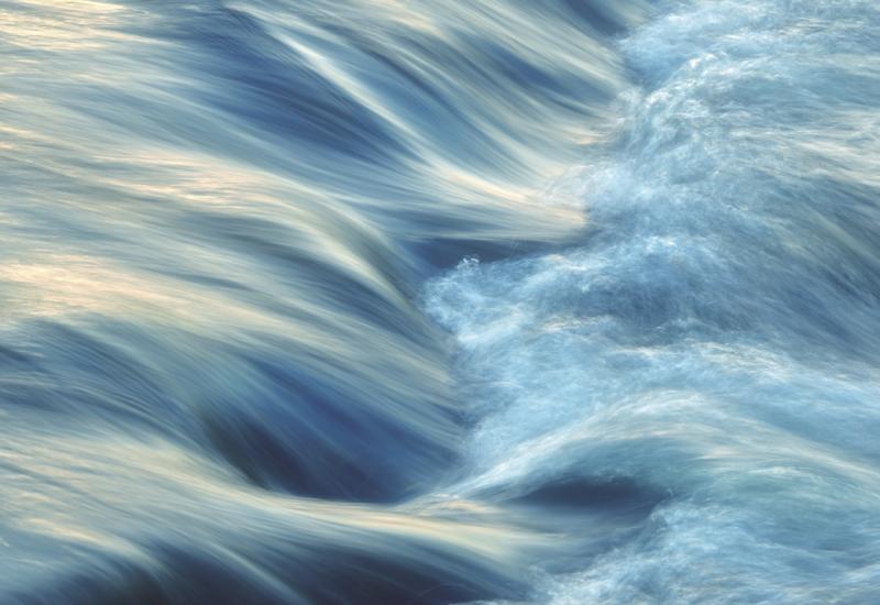 Das Bild zeigt einen Wasserstrom, der eine Stromschnelle hinunterschießt.