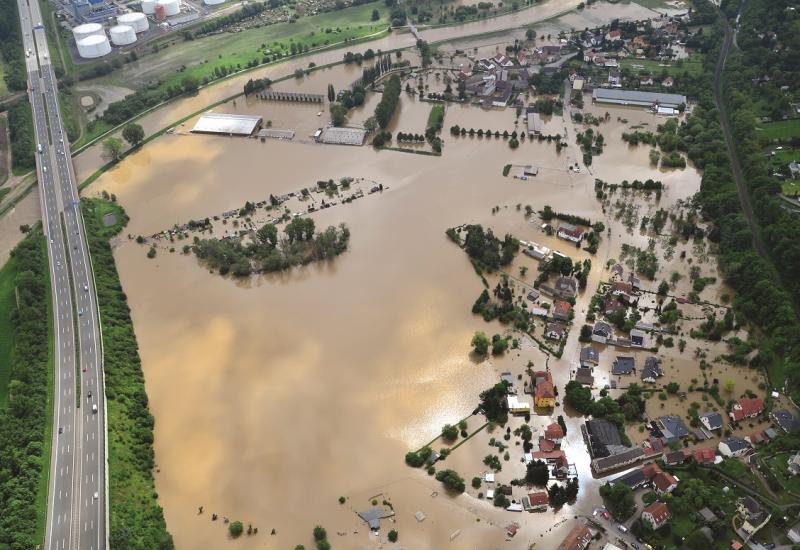 Das Bild zeigt die Luftaufnahme an einer großflächig von einem Hochwasser überfluteten Landschaft. Die Siedlungsgebiete stehen komplett unter Wasser.