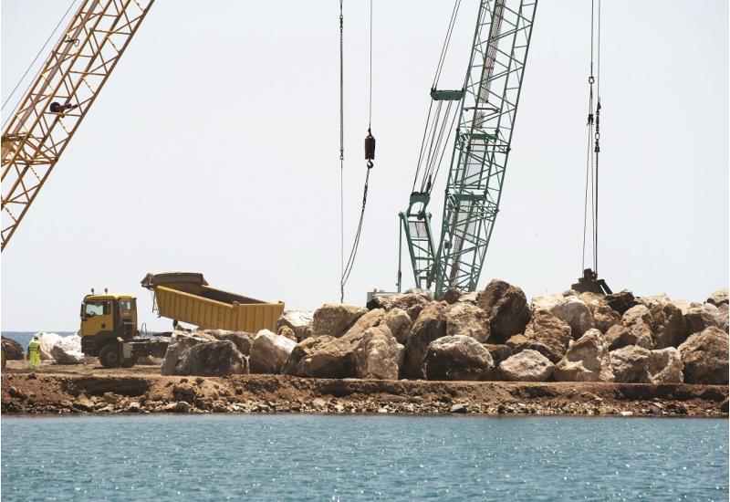 Das Bild zeigt eine große Baumaßnahme am Meer. Von großen Krananlagen und einem großen LKW werden große Steinblöcke bewegt.