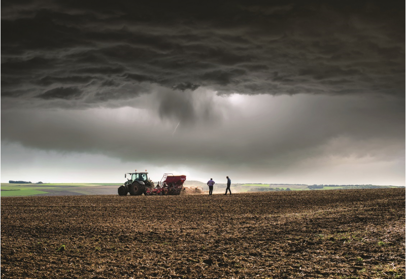 The picture shows a field in the foreground. A tractor is sowing and two men are checking the sowing. In the background, a wider agricultural landscape can be seen. The sky is very dark, a thunderstorm is approaching.