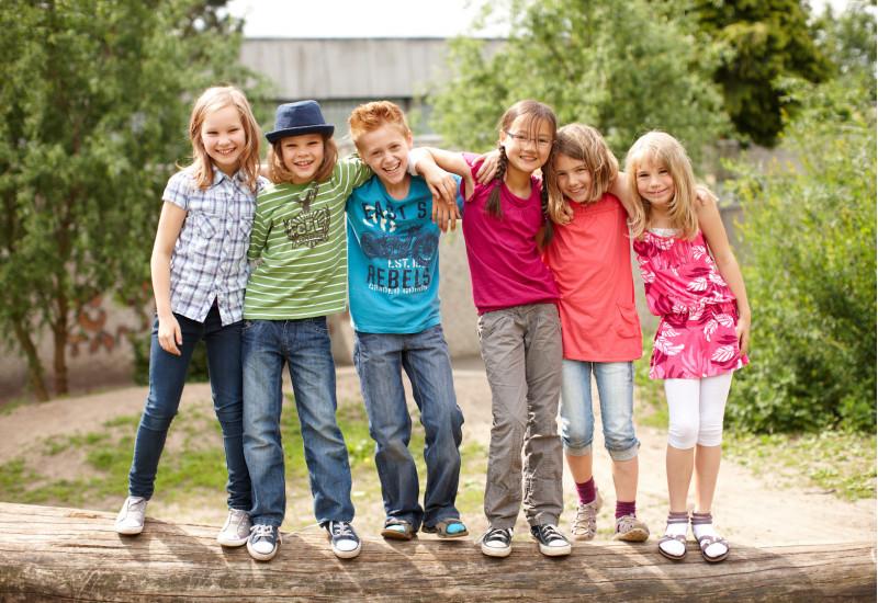 6 Kinder stehen lachend auf einem liegenden Baumstamm für ein Gruppenfoto, die Arme jeweils auf den Schultern des Nachbarn