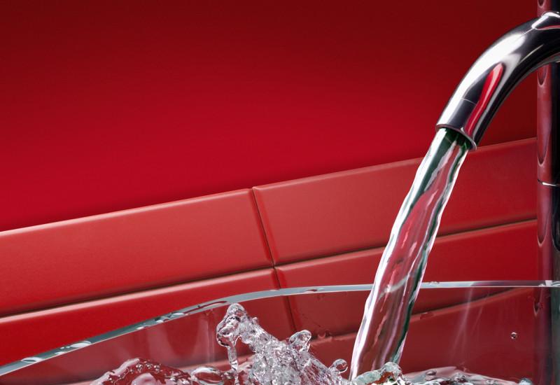 Laufender Küchenwasserhahn mit Glasschale, roter Hintergrund