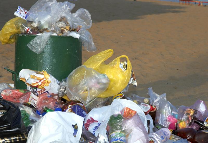 Überquellender Mülleimer am Strand