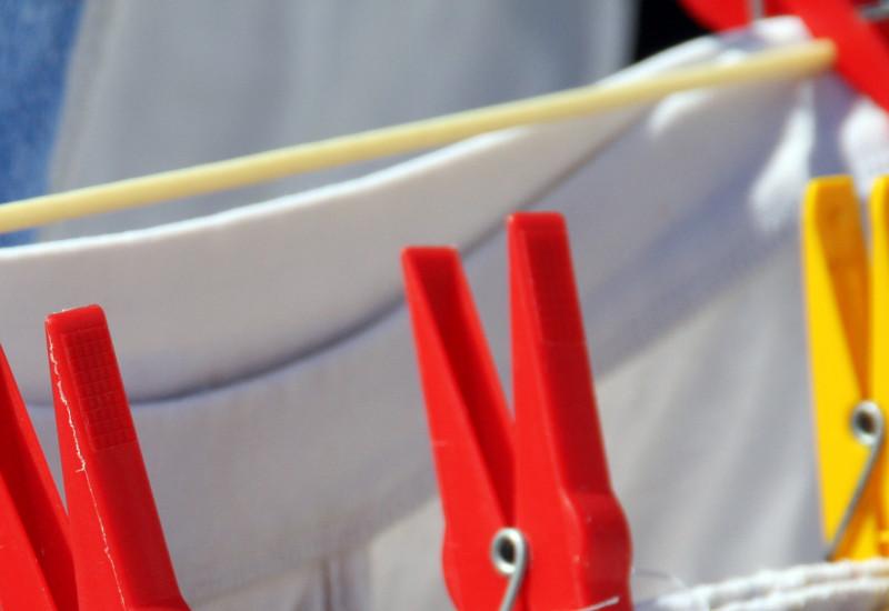 Weiße Hantücher hängen mit Wäscheklammern an einer Wäscheleine im Garten