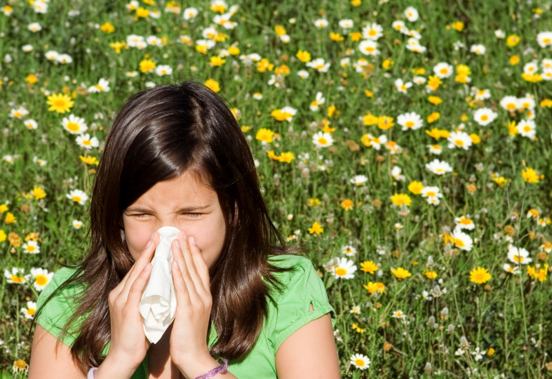 A girl blows her nose. In the background is a flower meadow with daisies an dandelion.