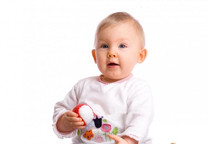 Ein Baby sitzt neben Kuscheltieren, es hält einen Ball in der Hand und guckt erwartungsvoll nach oben.