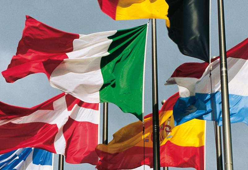 wehende Flaggen der Länder Schweiz, Griechenland, Spanien, Luxemburg, Italien, Niederlande, Portugal, England und Belgien sowie der Europäischen Union
