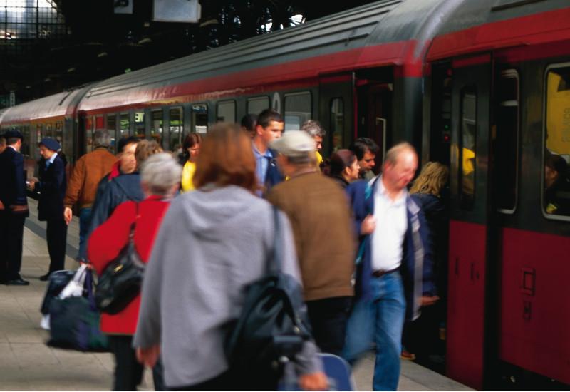 Zug im Bahnhof mit Menschengruppen am Gleis