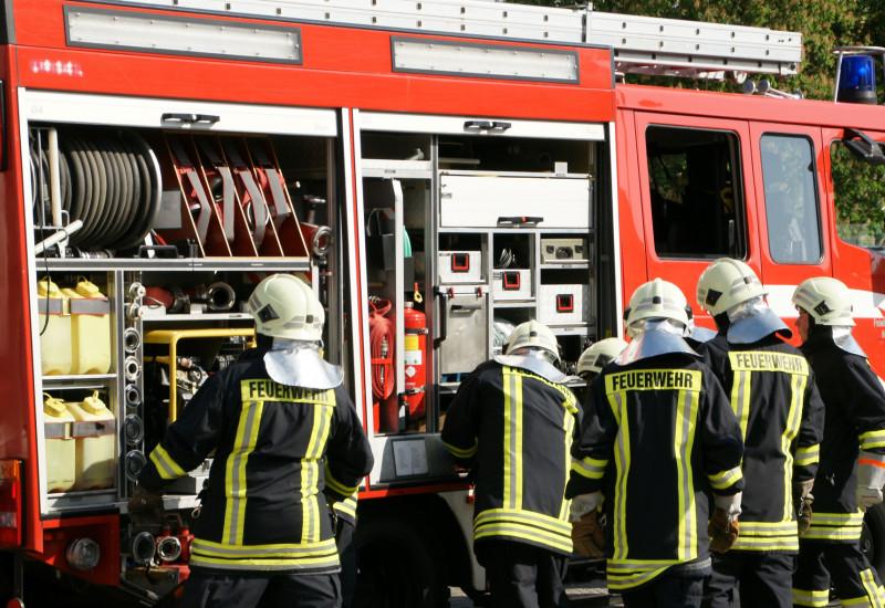 Feuerwehrmänner an einem Feuerwehrwagen