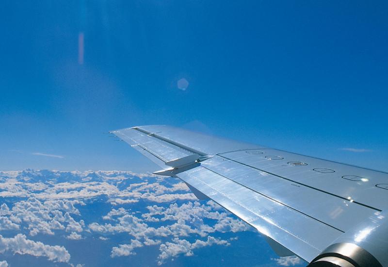 rechter Flugzeugflügel über den Wolken bei blauem Himmel