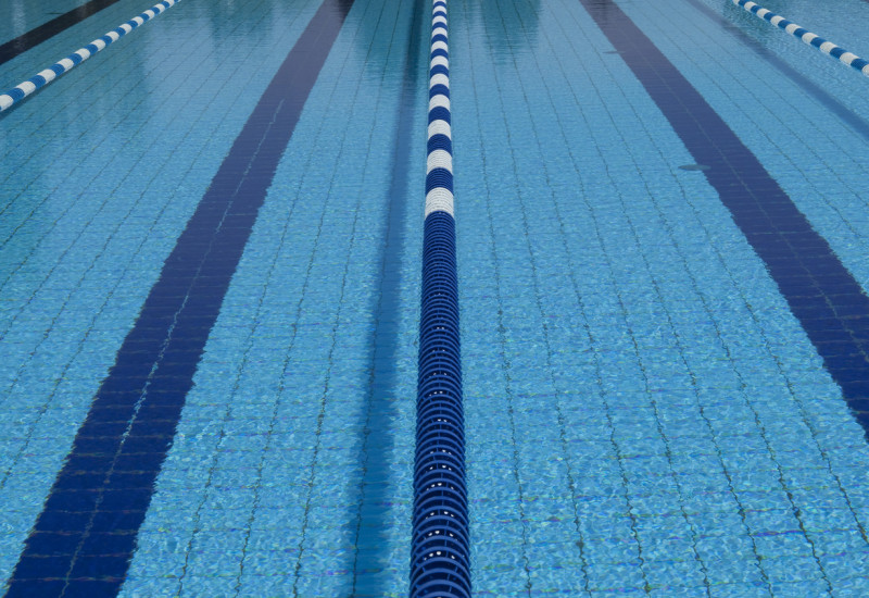 Das Wasserbecken eines Schwimmbades, wo die Bahnen durch schwimmende Abgrenzungen voneinander abgetrennt sind. Nahaufnahme