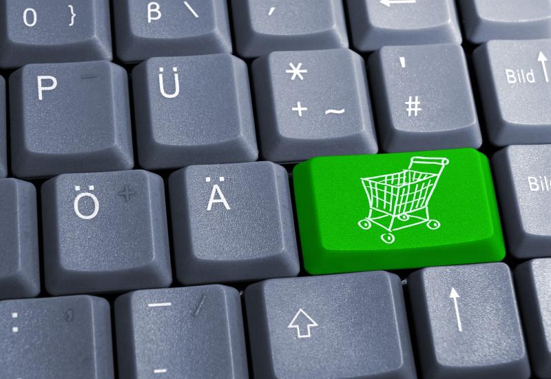 Computertastatur mit einer grünen Taste mit Einkaufswagen drauf