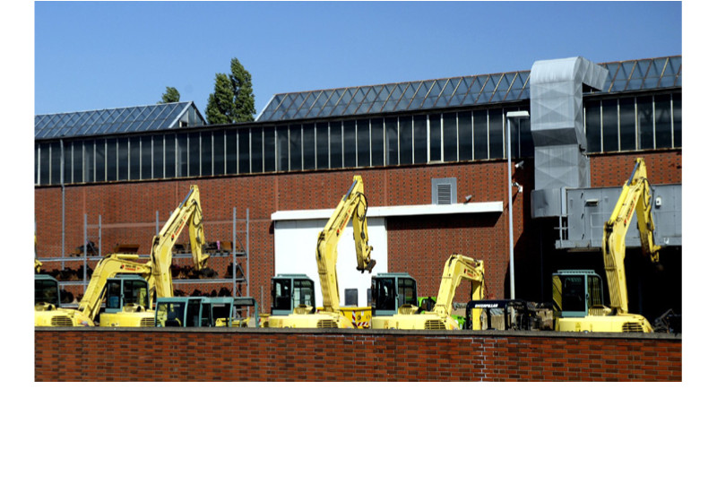 Sieben Bagger stehen auf einer Gewerbefläche vor einer Industriehalle