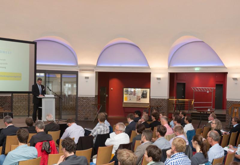 Viele Personen sitzen vor einer Bühne und hören einem Redner zu