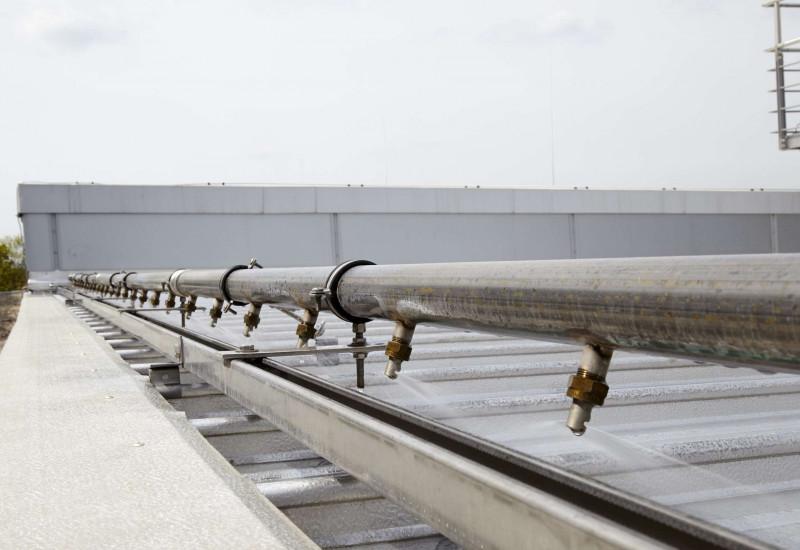 Dach wird über Rohrleitung mit Düsen mit Wasser besprenkelt.