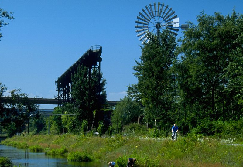 Ein Gewässer in einem Landschaftspark. Im Hintergrund steht ein Windrad. Im Vordergrund spielen Kinder in den Uferbereichen und fangen Fische.