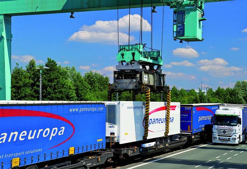 Paneuropa Anhänger werden von einem grünen Kran auf von Schienen auf die Straße verladen