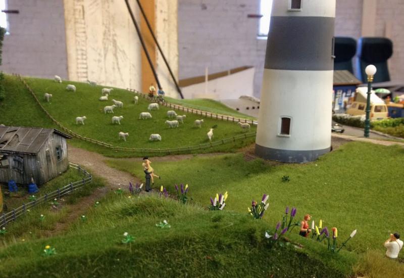 Deichanlage als Modell mit Leuchtturm, Schafen und Baggern