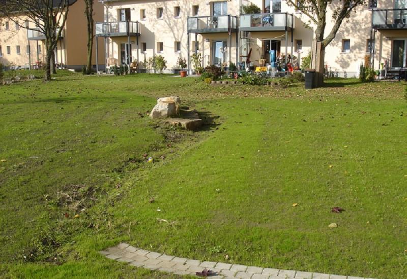 Auf dem Rasenboden verlaufen Rinnen für Regenwasserabfluss. Im Hintergrund stehen Wohnhäuser mit Terassen zum Rasen hin.